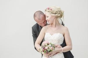 Brautpaar Kuss Strauss Kleid Spitze Hochzeitsfoto Zopf Frisur